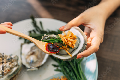 Fresh Oyster in shell in hand that topping with fried shallot, chili paste, Acacia Pennata and Thai style seafood sauce Canvas Print