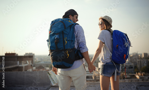 obraz lub plakat Multiethnic traveler couple using map together on sunny day