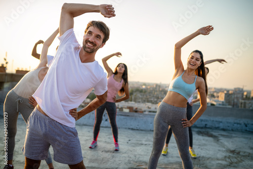 Deurstickers Hoogte schaal Group of friends fitness training together outdoors living active healthy