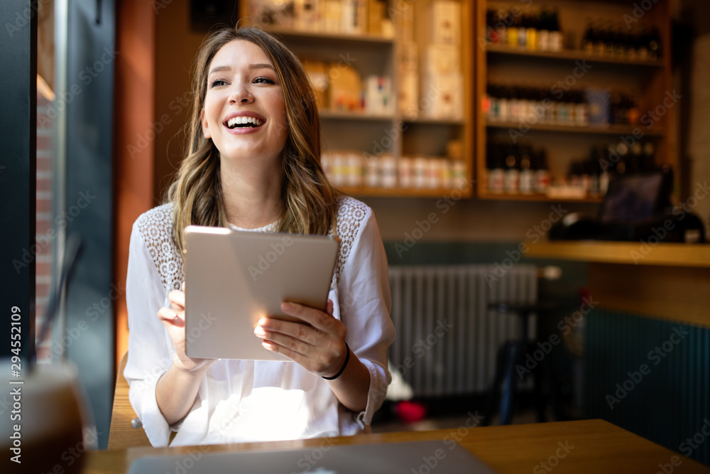 Fototapeta Happy girl working online or studying and learning while using tablet