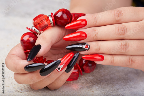 Hands with long artificial manicured nails colored with red and black nail polis фототапет