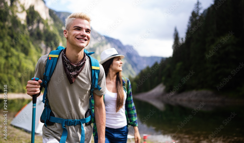 Smiling friends walking with backpacks. Adventure, travel, tourism, hike and people concept.