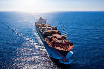 Luftaufnahme ein beladenen Containerschiffes bei voller Fahrt über blauem Meer