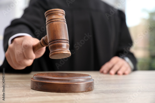 Judge with gavel at wooden table indoors, closeup. Criminal law Tableau sur Toile