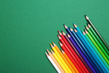 Fototapeta Rainbow - Color pencils on green background, flat lay. Space for text