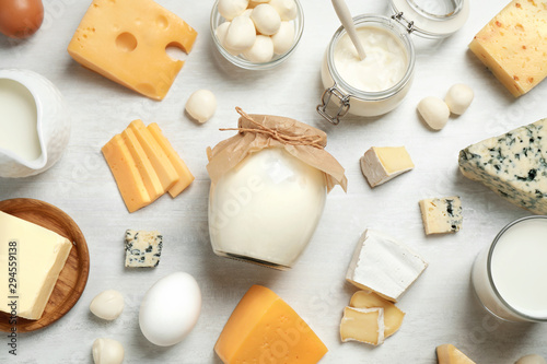 Different delicious dairy products on white table, flat lay