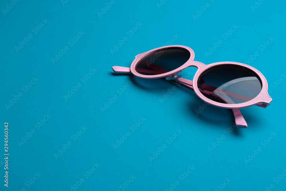 Fototapeta Stylish sunglasses on blue background, space for text. Fashionable accessory