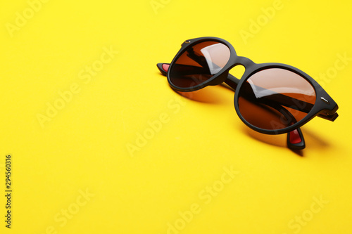 Stylish sunglasses on yellow background, space for text. Fashionable accessory - 294560316
