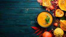 Pumpkin Soup With Pumpkin And Colored Autumn Leaves. Flat Lay. On A Blue Wooden Background. Top View. Free Space For Your Text.