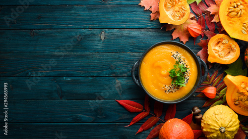 Valokuva Pumpkin soup with pumpkin and colored autumn leaves