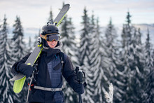 Portrait Of Professional Sportsman In Helmet And Goggles Carrying On His Shoulders Pair Of Skis. Male Skier Standing On Mountain Top. Grey Snowy Pine Trees On Blurred Background.