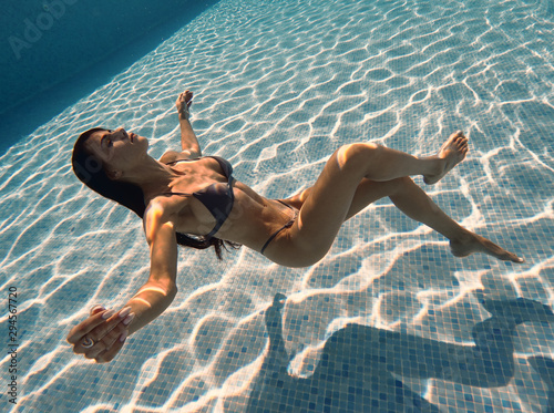 Young slim brunette woman having slim body wearing swimsuit swimming posing motionless inside of swimming pool on the depth, underwater photography, beauty, lifestyle concept