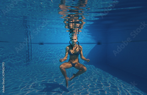Young pretty slim brunette woman wearing swimsuit do meditation on the depth of swimming pool, girl with folded fingers gesture symbol of yoga practice, healthy lifestyle body and mind health concept