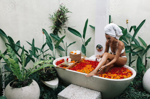 Obraz Woman relaxing in outdoor bath with flowers in Bali spa hotel. - fototapety do salonu