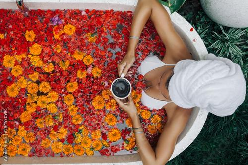 Billede på lærred Woman relaxing in outdoor bath with flowers in Bali spa hotel.