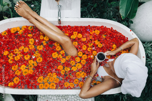 Photo Woman relaxing in outdoor bath with flowers in Bali spa hotel.