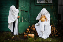 Two Ghost Covered With A White Ghost Sheet With Pumpkins In An Autumn Garden For Halloween Party. Halloween Concept.