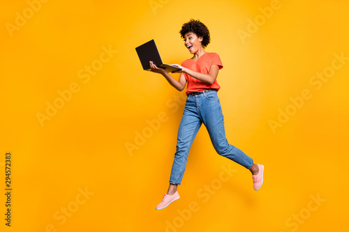 Fototapeta Full length photo of excited funny funky curly hair girl use her laptop find news information about sales jump wear denim jeans stylish trendy sneakers t-shirt isolated over yellow color background obraz na płótnie