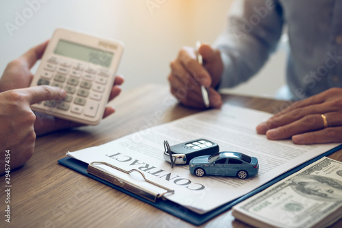 Carta da parati  Finance manager of the car showroom is calculating the cost of reserving a new car for the customer while signing a car purchase contract