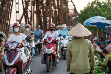 Vietnamese woman with traditional cone hat walking on Long Bien bridge busy street