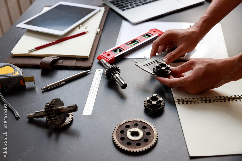 Fototapeta Engineer discussing and designing about mechanical gear parts in office.