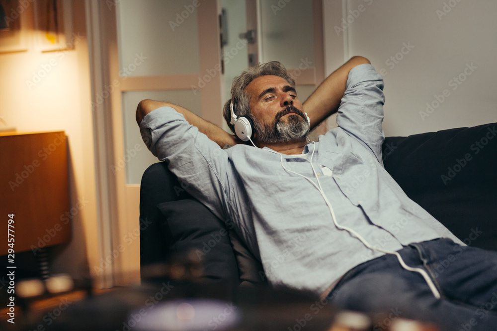 Fototapeta mid aged man relaxing home and listening music