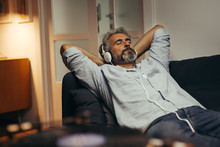 Mid Aged Man Relaxing Home And Listening Music