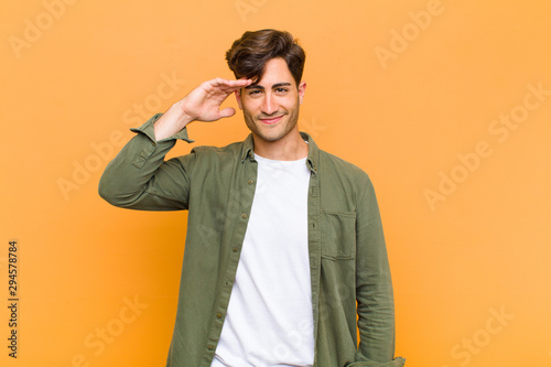 young handsome man greeting the camera with a military salute in an act of honor Billede på lærred