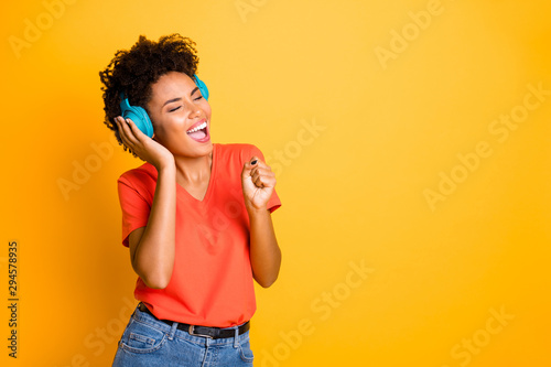 Copyspace photo of curly wavy cheerful charming lady singing into her imaginary microphone wearing jeans denim wireless earphones isolated over yellow vibrant color background - 294578935