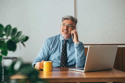 Fototapety, obrazy: senior manager talking on mobile phone while sitting desk in his office