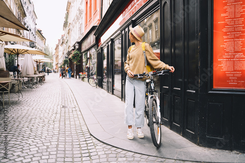 Leinwand Poster Girl with backpack and bicycle explores Ljubljana