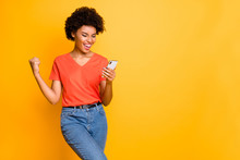 Copyspace Photo Of Fashionable Stylish Trendy Cheerful Champion Curly Wavy Having Received Feedback Looking At Phone Screen Wearing Jeans Denim Orange T-shirt Isolated Yellow Vivid Color Background