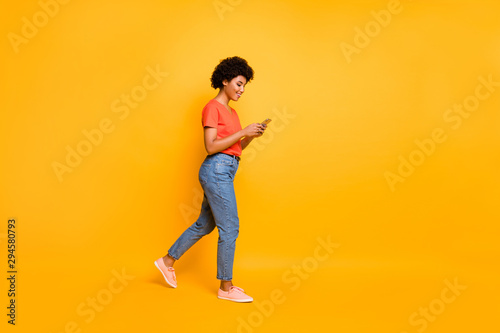 Poster Individuel Side profile photo of cheerful cute attractive young influencer browsing through her telephone wearing jeans denim orange t-shirt sneakers isolated over vibrant color background