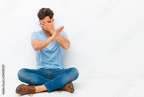Fotografia, Obraz  young handsome man covering face with hand and putting other hand up front to st