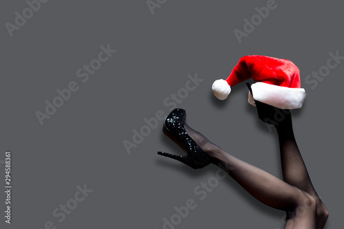 Fototapeta Mrs santa claus legs in black stockings with christmas hat isolated on grey background, minimal style, copy space obraz