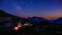 TIMELAPSE: Blurry Car Lights Moving Along Mountain Road Under The Starry Sky.