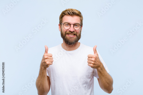 Obraz young blonde adult man smiling broadly looking happy, positive, confident and successful, with both thumbs up - fototapety do salonu