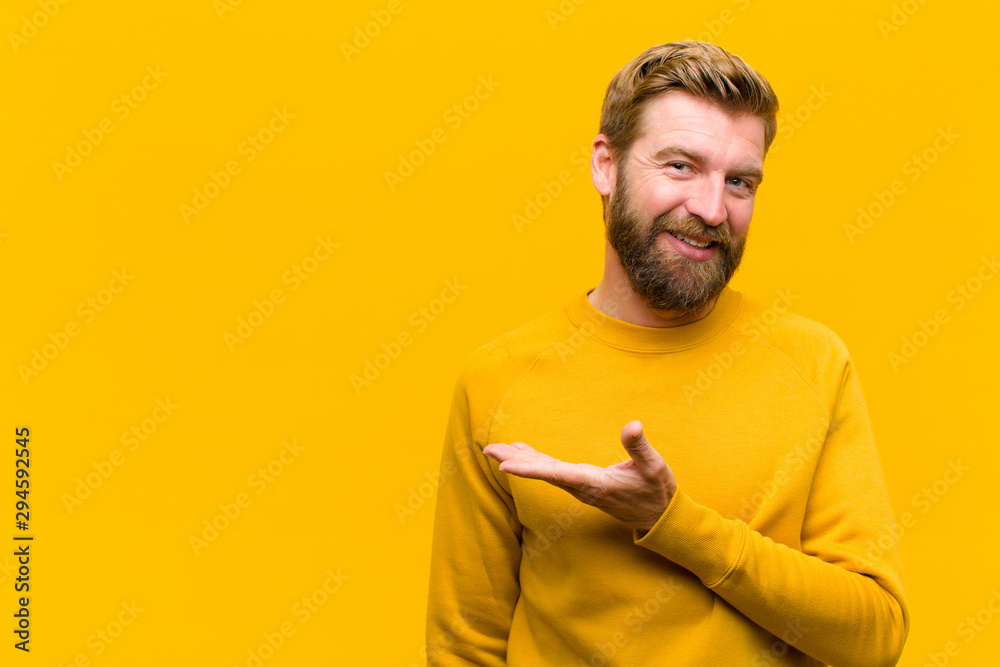 Fototapeta young blonde man smiling cheerfully, feeling happy and showing a concept in copy space with palm of hand against orange wall