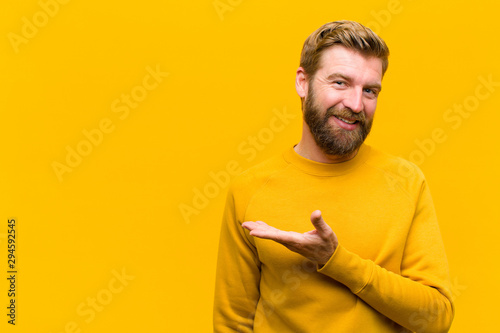 Fototapeta young blonde man smiling cheerfully, feeling happy and showing a concept in copy space with palm of hand against orange wall obraz
