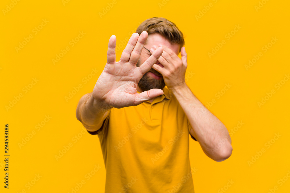 Fototapety, obrazy: young blonde man covering face with hand and putting other hand up front to stop camera, refusing photos or pictures against orange wall