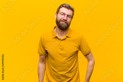 Fotografía  young blonde man smiling cheerfully and casually with a positive, happy, confide