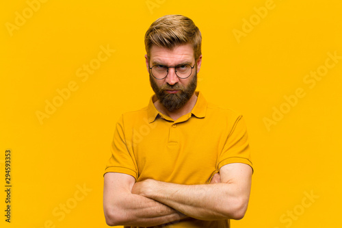 young blonde man feeling displeased and disappointed, looking serious, annoyed a Wallpaper Mural