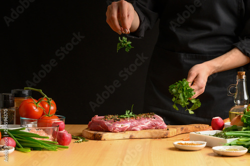 Pork steak and green herbs, Italian parsley from the chef in the background. Horizontal photo. With vegetables, tomatoes, hot peppers, onions and a chapel. With black background
