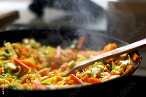 Cooking carrot, pumpkin, zucchini nad leek in wok. Selective focus, close-up.