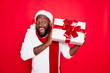 canvas print picture - Portrait of amazed funky dark skin man wear santa claus headwear hold big package receive on x-mas time celebration scream wow feel interested wear style pullover isolated over red color background
