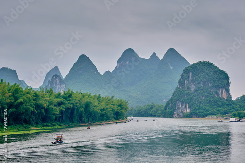 Fotobehang Donkergrijs Tourist boats on Li river with carst mountains in the background
