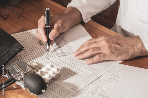Cropped image of male doctor's hands writing medical prescription and updating m Canvas Print
