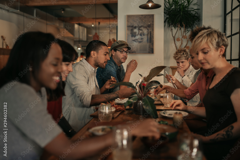 Fototapety, obrazy: Diverse friends talking over a bistro dinner at night