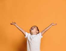 Excited Kid Boy In White T-shirt With His Hands Up Wide Spread Is Catching Something. Free Copy Space On Yellow