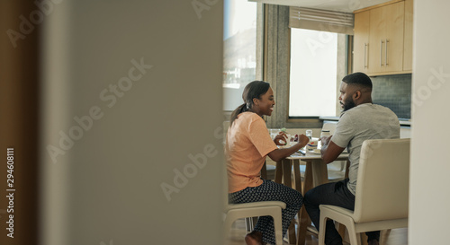 Smiling young African American couple talking together over breakfast Poster Mural XXL
